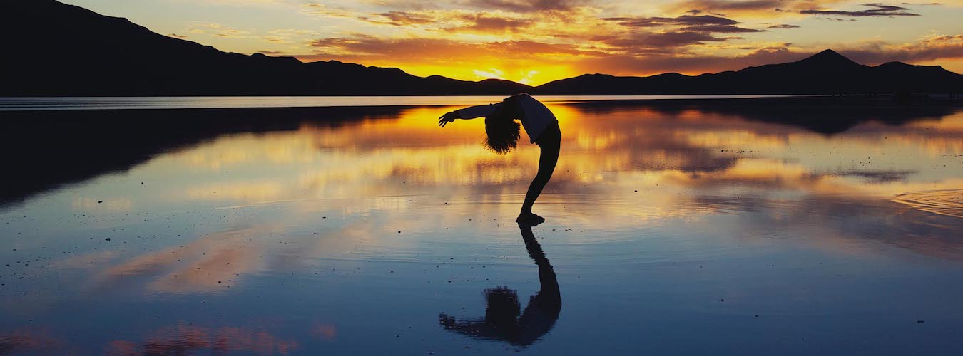 Woman doing a backbend at sea with sunset