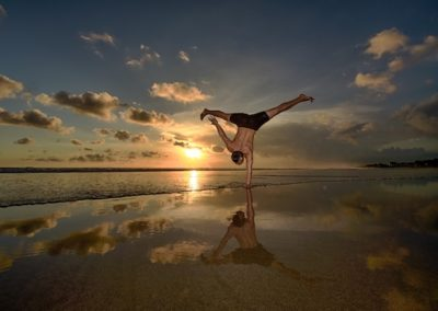 man doing a handstand on the beach in Canggu Bali