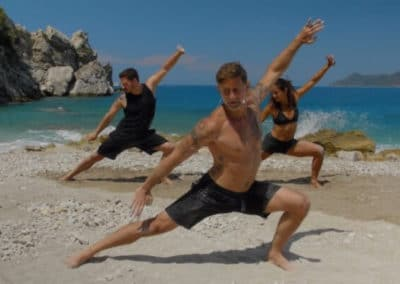 Yogis doing warrior 2 yoga asana on the beach with rocks and ocean in the background