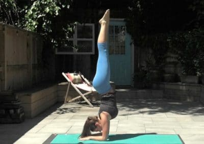 Yogi doing an arm stand on a yoga mat in a garden