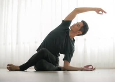 Yogi doing shoelace yoga asana while bending to his left side in a yoga studio
