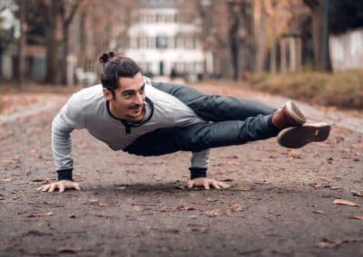 man doing side crow yoga asana