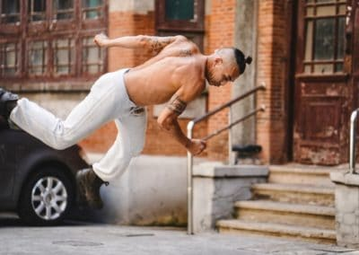 man topless in front of old brick building doing a jump
