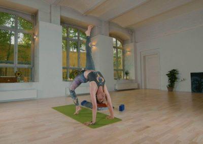 yoga teacher doing a bridge with one leg lifted