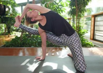 Yoga teacher stretching her right leg to the side with green plants in the background