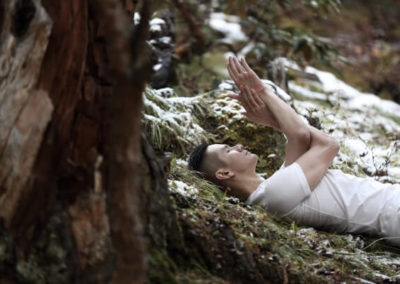 Chris Su lying on the ground in a forest wearing all white doing eagle pose with his arms