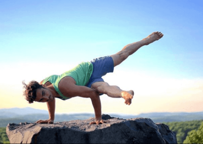 Matt Giordano doing a flying hip opening on a rock