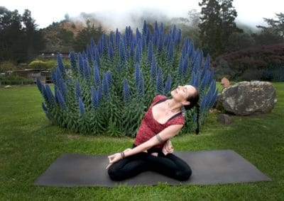 Katchie Ananda stretching on a yoga mat outside in front of flowers and trees