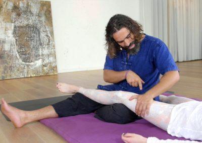 Thai massage expert massaging leg of a patient while explaining the technique