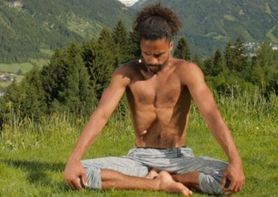 yogi sitting with crossed legs on meadow in the alps inhaling