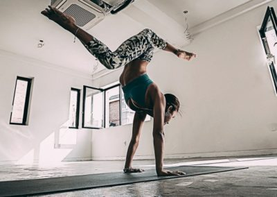 women doing a handstand with bended legs in an empty white room