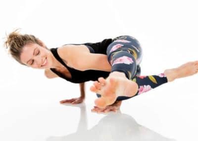 Yoga teacher Alexandra Harfield doing side crow yoga asana in professional photography studio