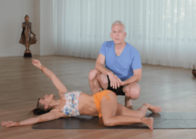 Desi Springer lying on a yoga mat showing a yoga asana and John Friend explaining the asana