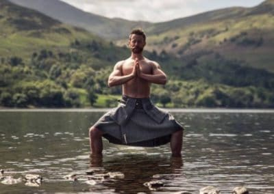 Finlay Wilson topless in Scottish tilt standing in low water with green hills in the background