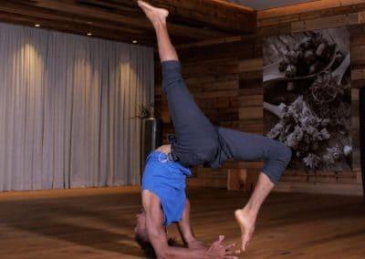 Yogi doing a bridge with one leg lifted