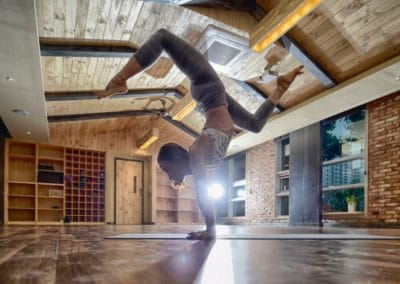 women doing a handstand with bended legs in a wooden yoga studio