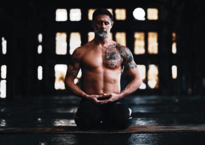 Cameron Shayne meditating in dark abandoned building