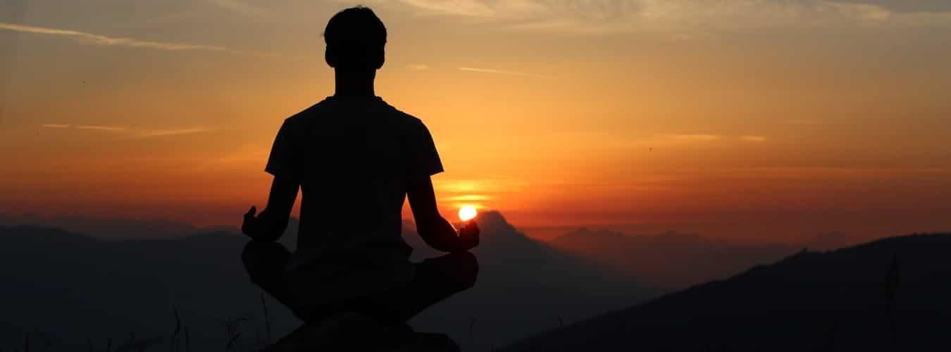 Mann sitzt in Meditation bei Sonnenuntergang im Gebirge