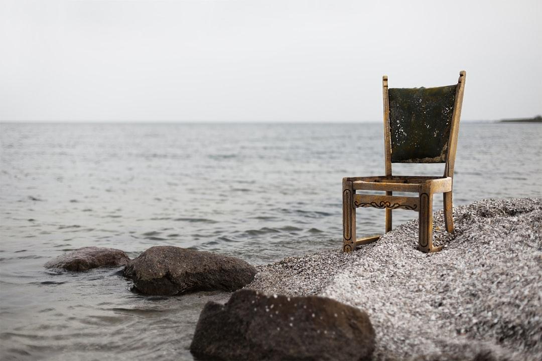Wooden chair on sandbar at sea