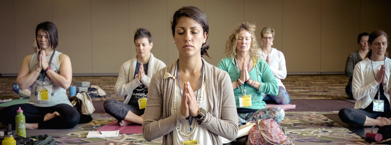 Group of 8 female yoga students sitting in meditative pose