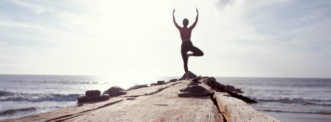 Frau in der Yogapose Baum auf Steg am Meer