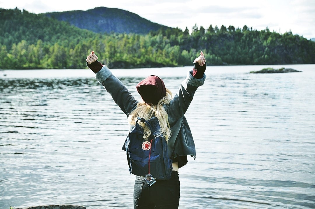 Woman with backpack victoriously raising arms up on waterfront