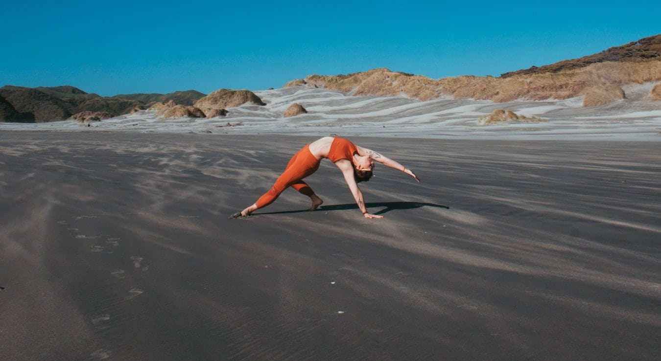 Woman performing Wild Thing yoga pose in grey sand desert