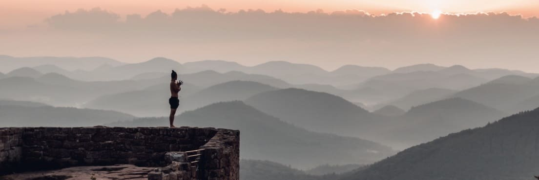 Young Ho Kim standing on a wall surrounded by mountains