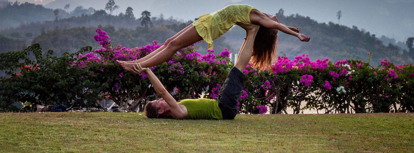Couple doing AcroYoga Whale pose in front of purple-flower hedge