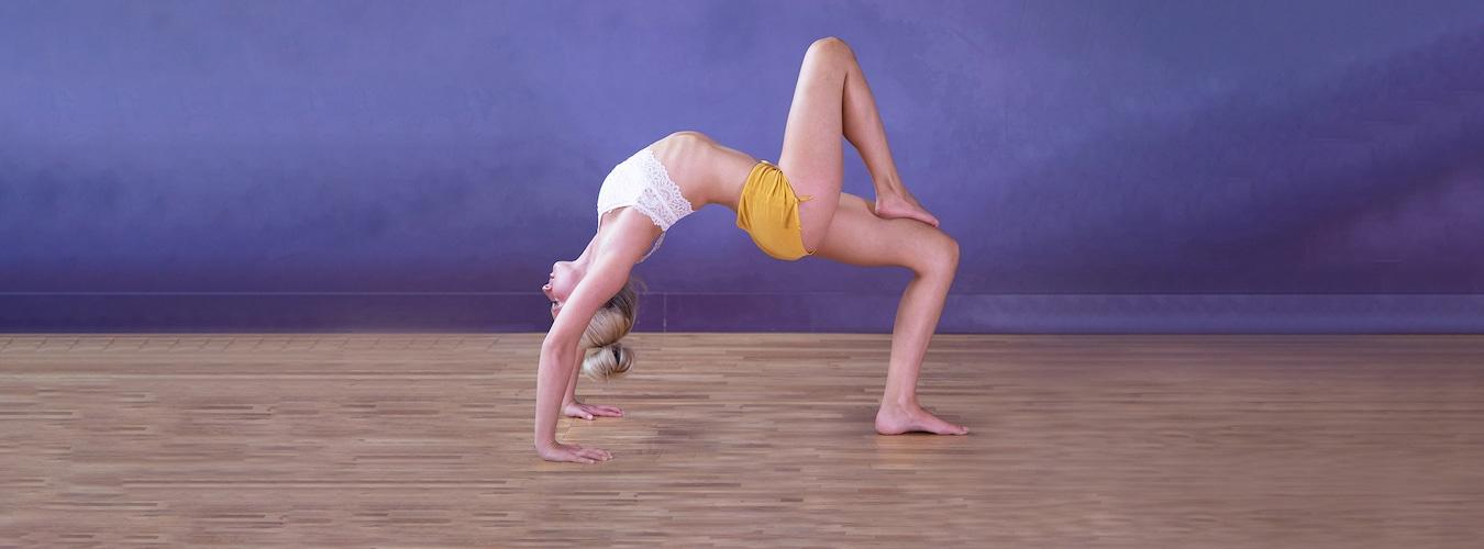Woman doing one-legged Wheel yoga pose