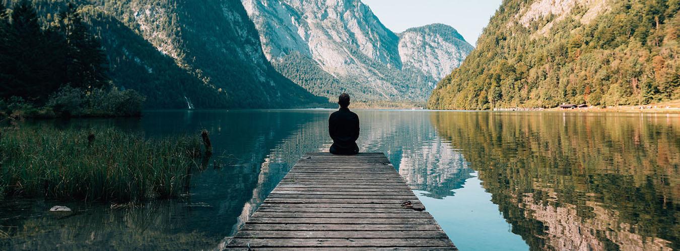 Man sitting on a dock at a mountain lake