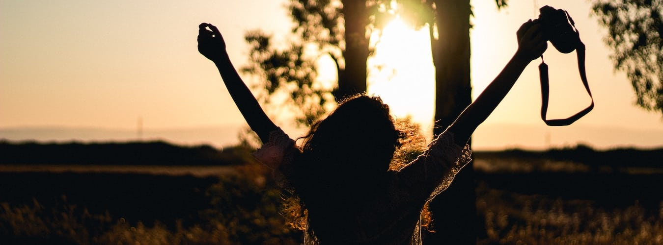 Silhouette of a woman raising her hands up at sunset