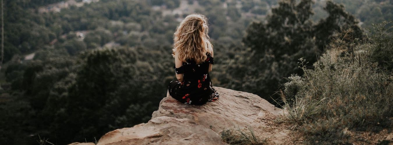 Frau sitzt auf Felsvorsprung in Landschaft