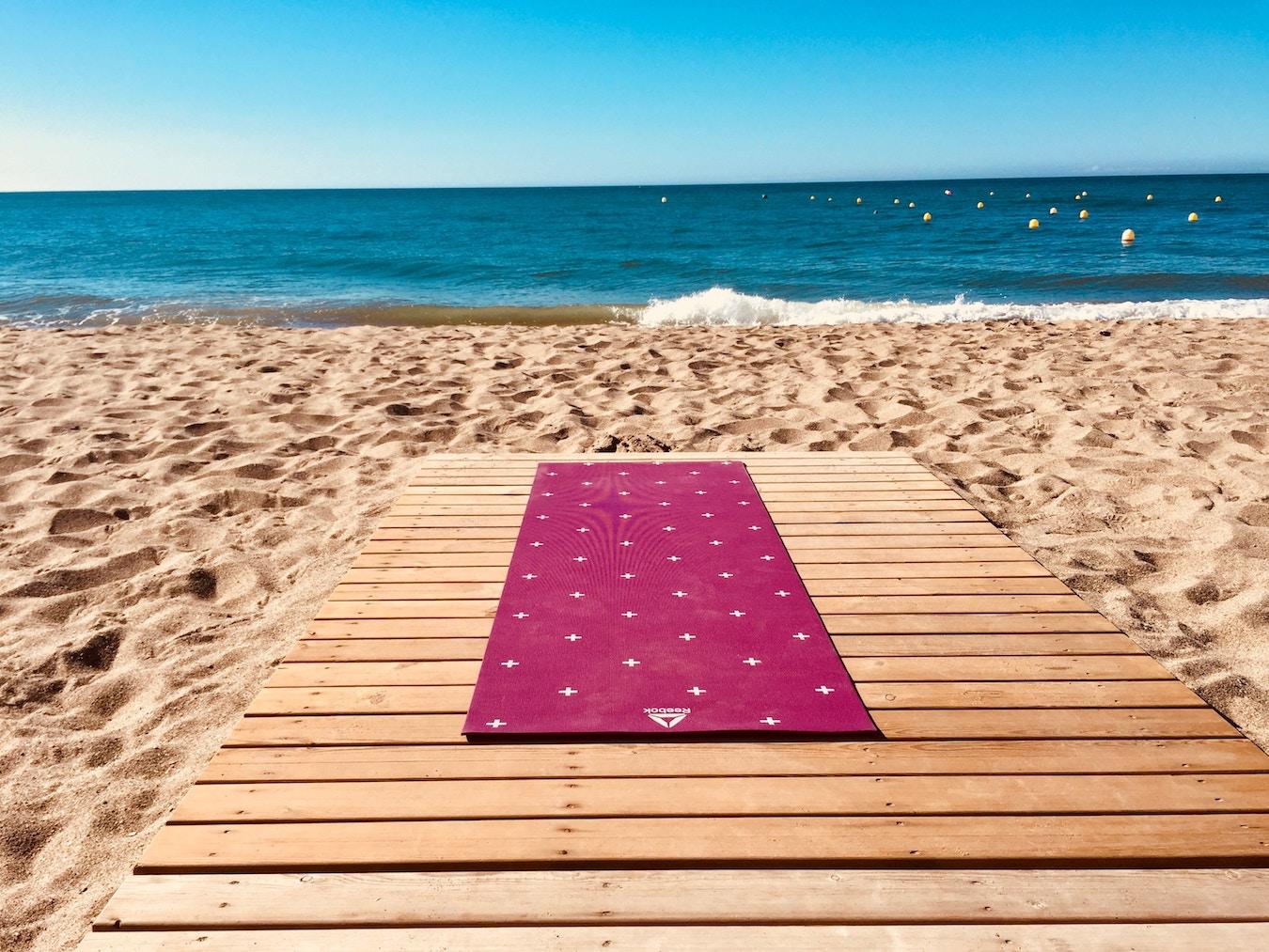 Leere Yogamatte pink auf Holzsteg am Strand