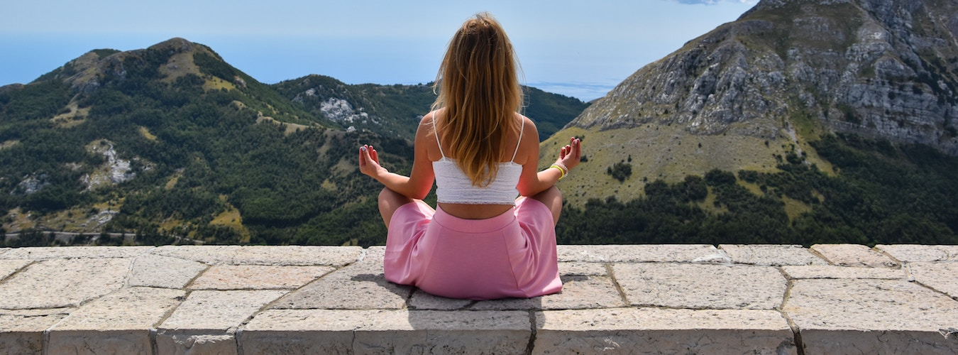 Woman meditating on stone wall in mountain scenery