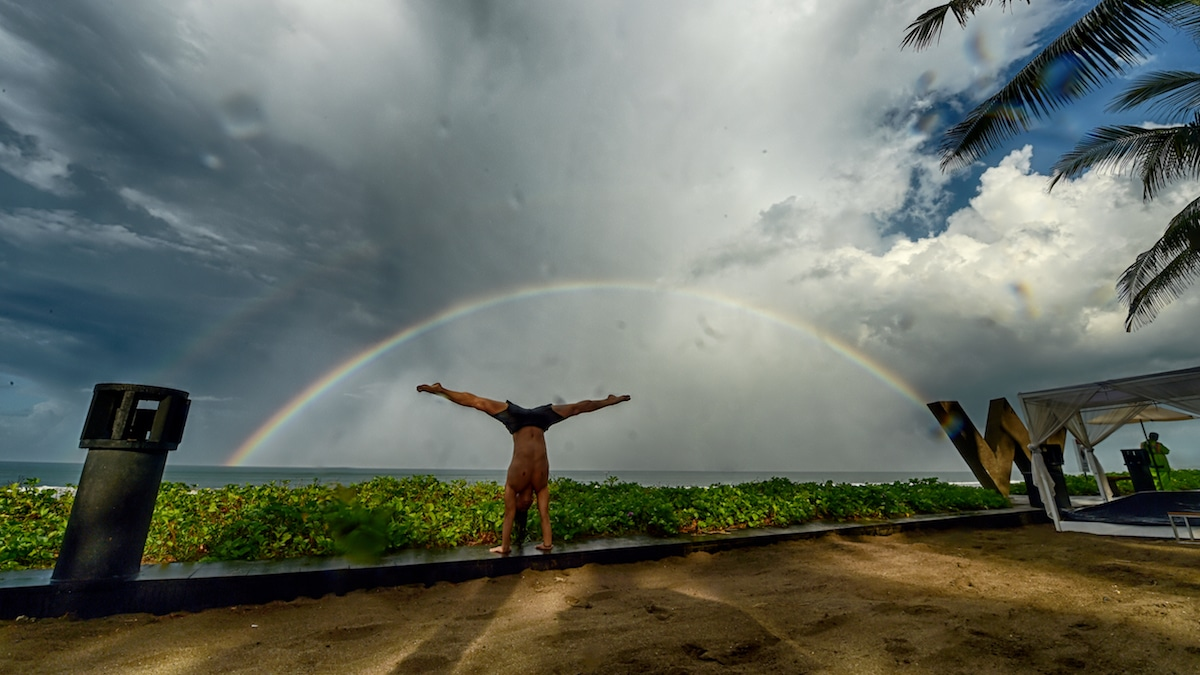Young Ho Kim doing handstand at sea in front of rainbow