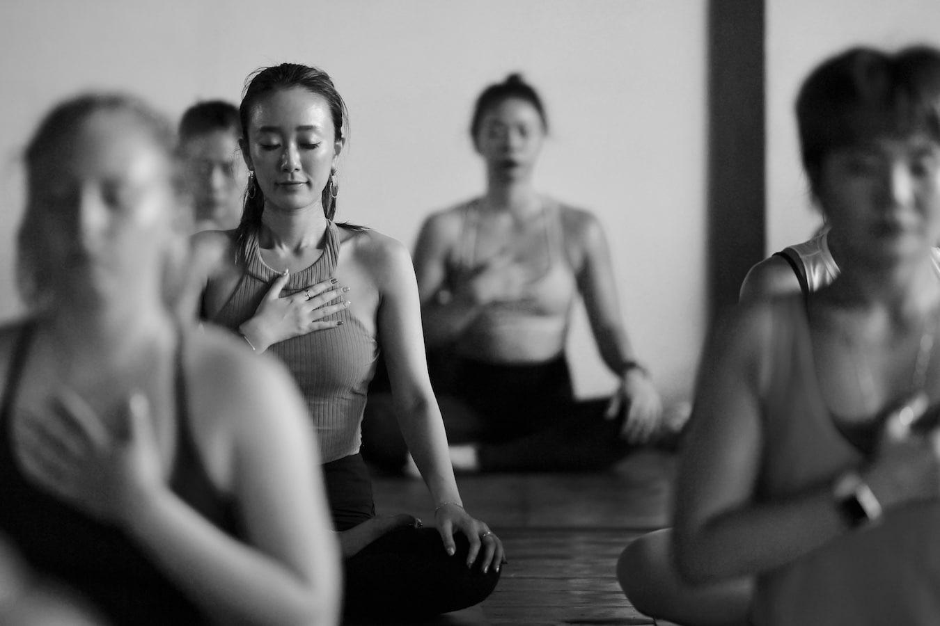 Yogaklasse im Schneidersitz sitzend mit Hand auf Herz