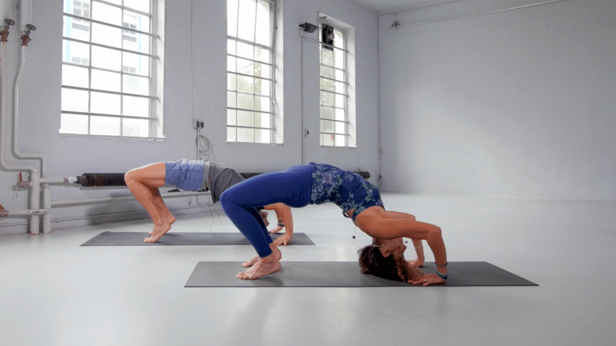 Desiree Rumbaugh and Andrew Rivin in a Wheel pose variation with head on the floor