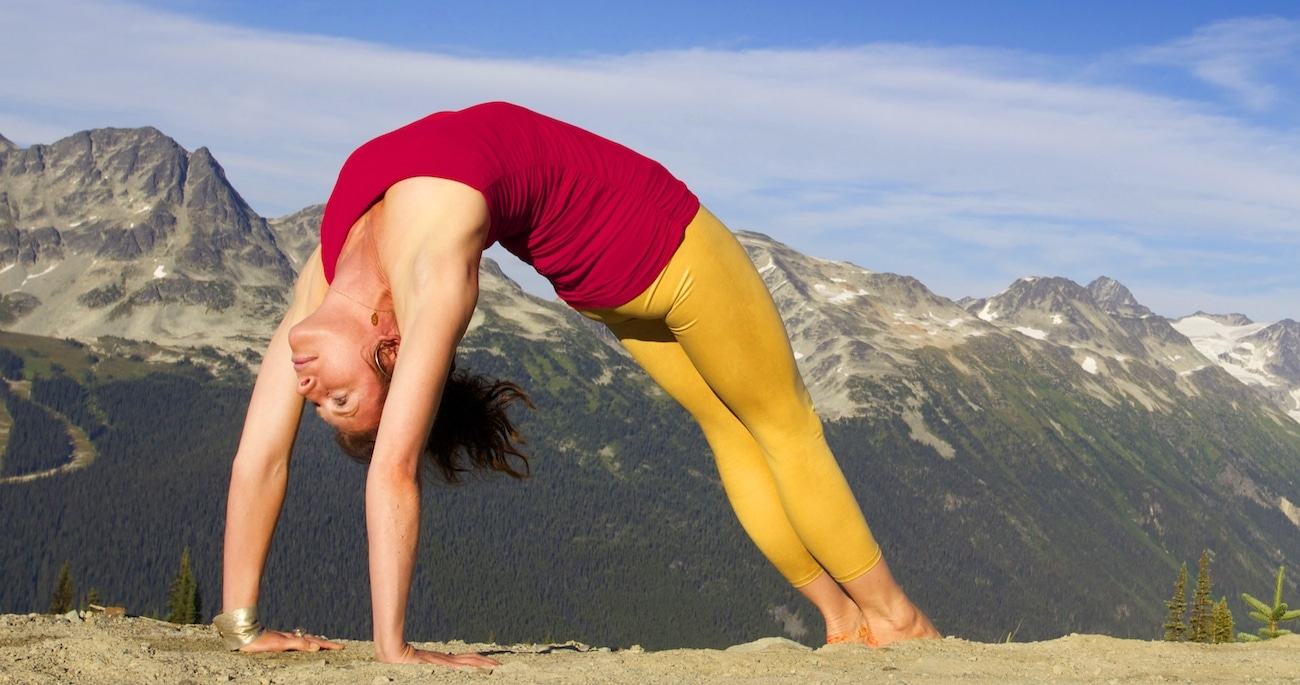 Sianna Sherman in der Yogapose Rad in Berglandschaft