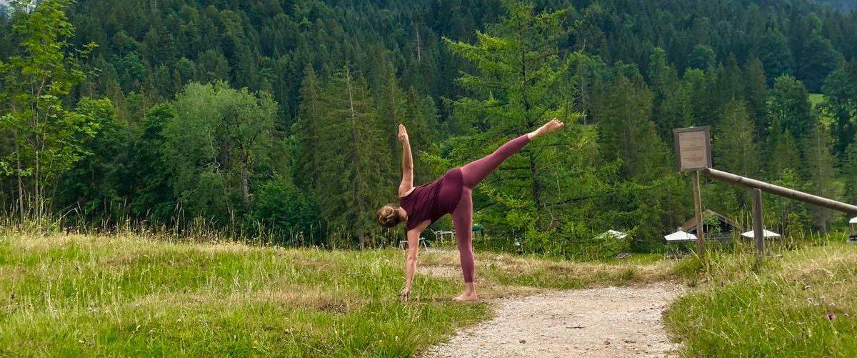 Woman doing Half Moon pose in mountain scenery