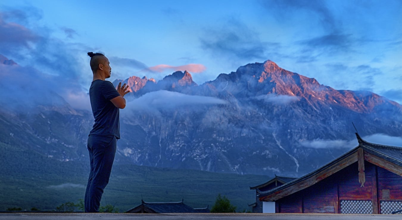 Young Ho Kim standing in a mindful yoga pose in mountain scenery