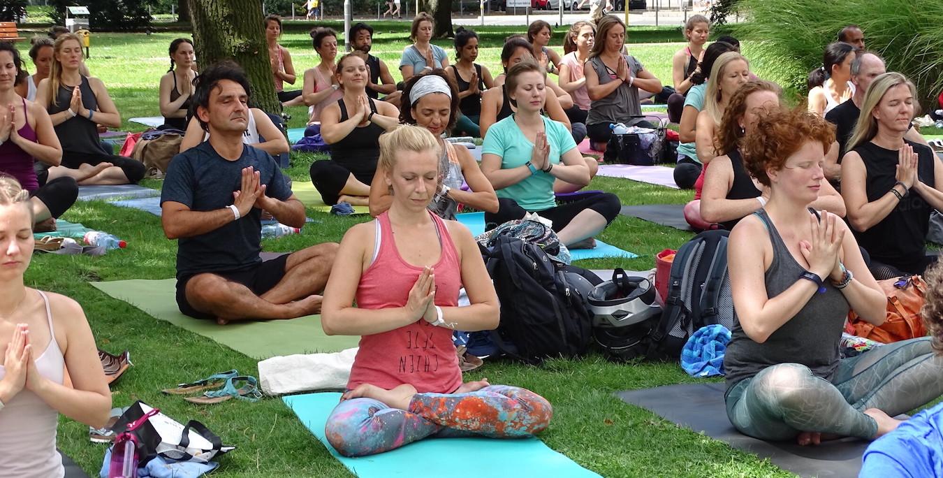 Outdoor-Yogaklasse beim Meditieren im Sitzen mit verschränkten Beinen
